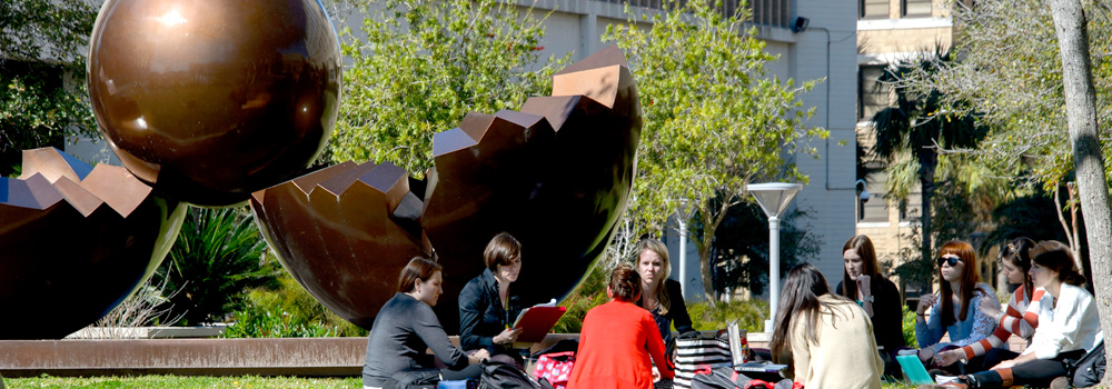 Students sitting by sculpture on campus